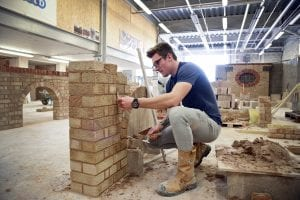 Construction student working on building a wall