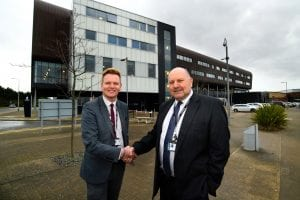 Furness College Principal and Chief Executive Professor Andrew Wren congratulates former Chair of Governors John Butler on his MBE for services to education
