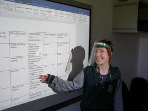 Tutor at Outreach pointing at a whiteboard