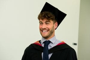 Smiling student wearing graduation cap and gown